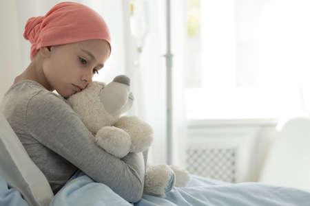 Débil niña con cáncer con pañuelo rosa y abrazando a osito de peluche