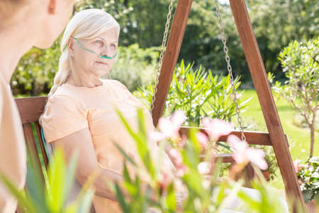 Weak elderly woman during treatment in the hospital's garden during summer Stock Photo - 109361556