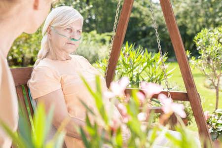Weak elderly woman during treatment in the hospitals garden during summer