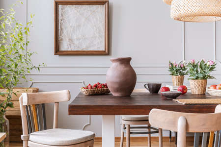 Wooden chairs at table with vase and flowers in grey dining room interior with poster. Real photo Foto de archivo