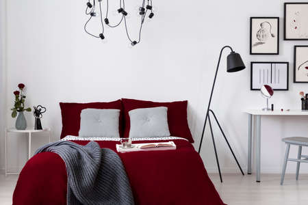 A burgundy bedding and gray pillows on a bed in a white wall bedroom interior. Real photo. Archivio Fotografico - 109161710