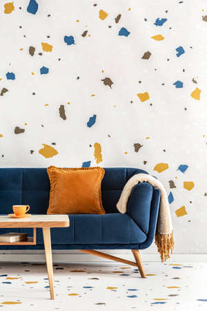 Wooden table in front of blue couch with orange pillow in colorful living room interior. Real photo Stock Photo