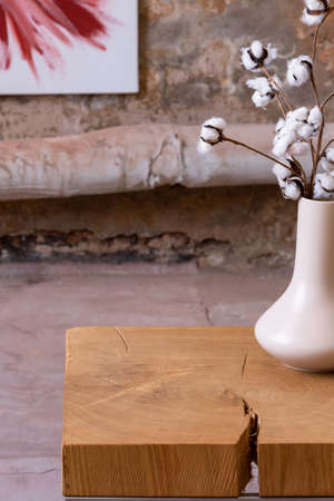 White flowers on wooden table in simple bedroom interior with poster. Real photo