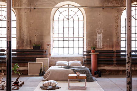 Table on rug in spacious bright bedroom interior with window above cushions on bed. Real photo Stock Photo