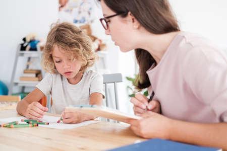 Ein Psychotherapeut, der ein Kind beim Zeichnen von Bildern mit Buntstiften während einer Bewertung in einer Privatschule beobachtet.