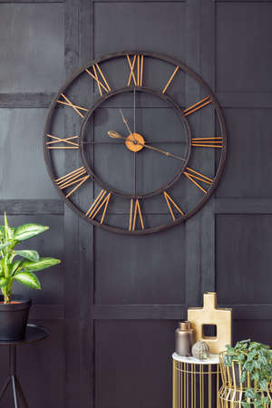 Real photo with close-up of big clock hanging on black wall in dark living room interior with gold accessories and fresh plants
