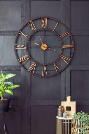 Foto reale con il primo piano del grande orologio appeso alla parete nera all'interno del soggiorno scuro con accessori in oro e piante fresche