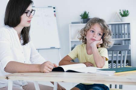 Ein zerstreutes Kind, das während eines Unterrichts mit einem Tutor zur Seite schaut und nicht auf sein Hausaufgabenheft.