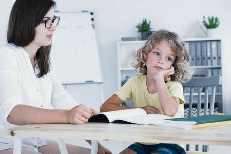 An absent-minded kid looking to the side and not at his homework notebook during a lesson with a tutor.