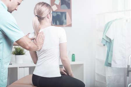 Professioneller Physiotherapeut, der Patienten mit einer krummen Wirbelsäule im Krankenhaus unterstützt Standard-Bild