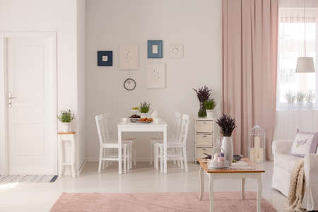 Flowers on table next to sofa in white and pink apartment interior with posters and drapes. Real photo