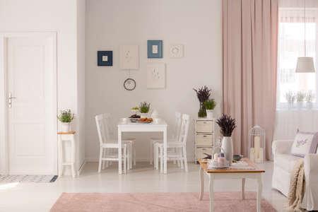 Flores en la mesa junto al sofá en el interior del apartamento blanco y rosa con carteles y cortinas. Foto real