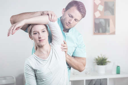 Professional physiotherapist and woman with pain of arm during physiotherapy