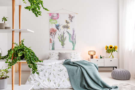 Green plants on shelves beside a bed dressed in white cotton bedding and teal blue blanket in a bright bedroom interior. Flowers and birds painted on the fabric above the bed. Real photo.