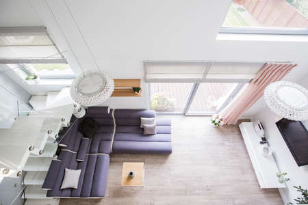 Top view of a living room interior with a comfy sofa, floor, glass door and tv. Real photo Foto de archivo