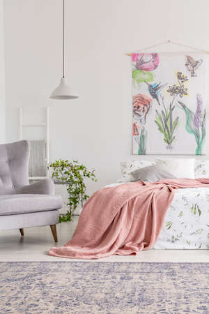 Cozy bedroom interior with a bed dressed in white and green sheets and peach blanket. Upholstered gray armchair beside the bed and painted fabric art on the back wall. Real photo. Фото со стока