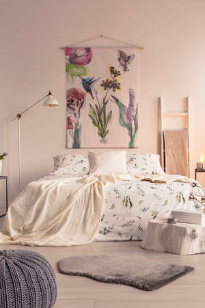 Vertical view of a pastel bedroom interior with a big bed in the middle and a painted fabric art on the wall. Real photo.