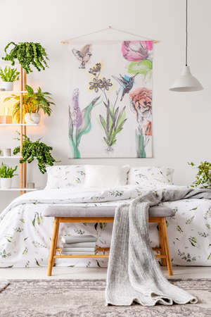 Urban jungle bedroom interior with a bed dressed in white and green bedding and painted art on the wall. Plants in pots beside the bed. Real photo. Фото со стока