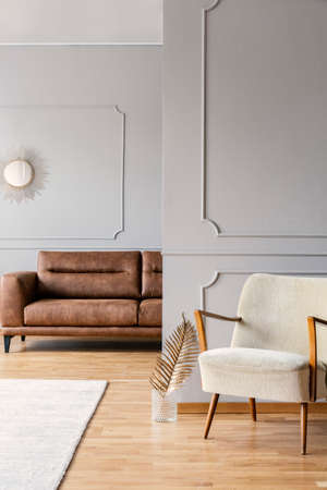 Vintage armchair in minimal living room of elegant apartment with brown leather sofa