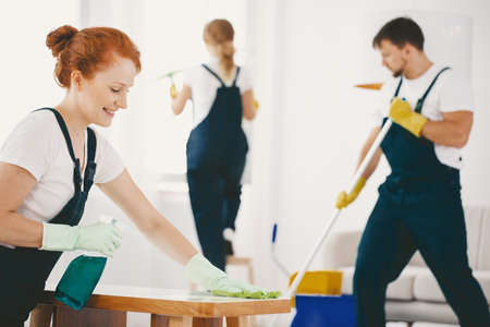 Smiling woman with gloves and spray cleaning table at home Stock Photo