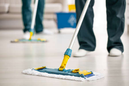 Close-up on mop on the floor holding by cleaning specialist while purifying interior 版權商用圖片