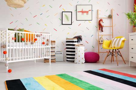 Tappeto colorato e sedia gialla all'interno della stanza del bambino con culla e poster su carta da parati. foto reale Archivio Fotografico - 109343920