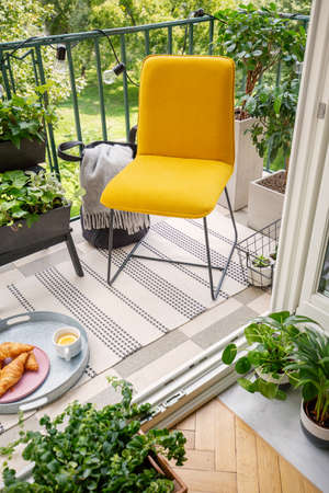 High angle view of a vibrant yellow chair and home plants on a peaceful balcony with string lights, sweet breakfast and a striped rug