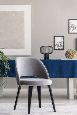 Modern chair at table with blue cloth in grey dining room interior with posters and lamp. Real photo Stock Photo - 109343925