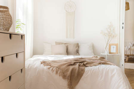 Blanket on white bed with pillows and wooden cabinet in minimal natural bedroom interior. Real photo Stock Photo