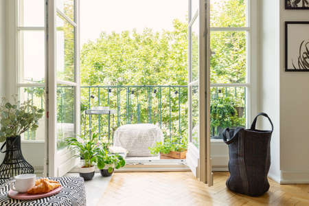 Open glass door from a living room interior into a city garden on a sunny balcony with green plants and comfy furniture