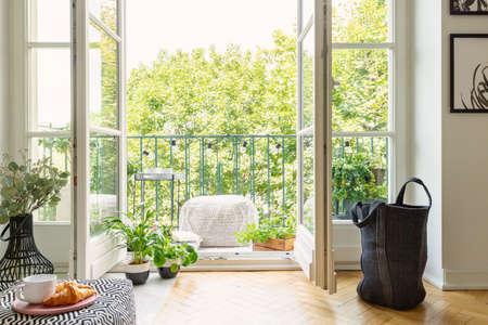 Porta a vetri aperta dall'interno di un soggiorno in un giardino cittadino su un balcone soleggiato con piante verdi e mobili confortevoli