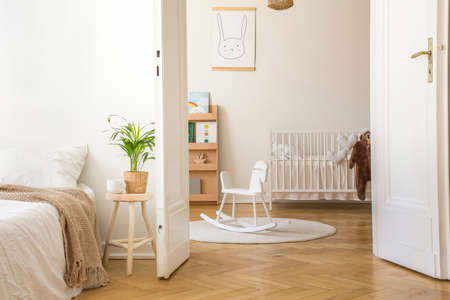 Plant on stool next to bed in white bedroom interior with rocking horse on rug and cradle. Real photo Stock Photo
