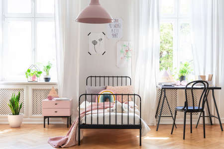 Chair at desk next to bed in pink and white girls room interior with plants and windows. Real photo Stockfoto