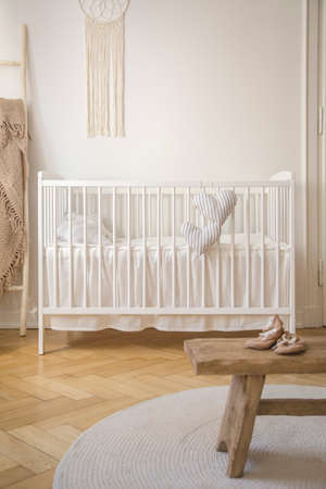 White cradle and shoes on wooden stool in babys bedroom interior with round rug. Real photo