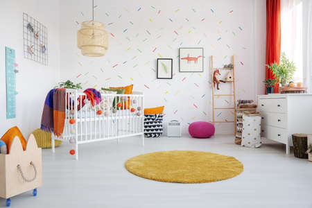 Orange round rug and posters in colorful kids room interior with cradle and wooden crate. Real photo