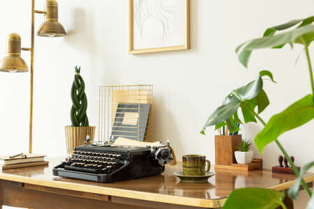 Typewriter, cup of coffee and plant on wooden desk in workspace interior with gold lamp. Real photo