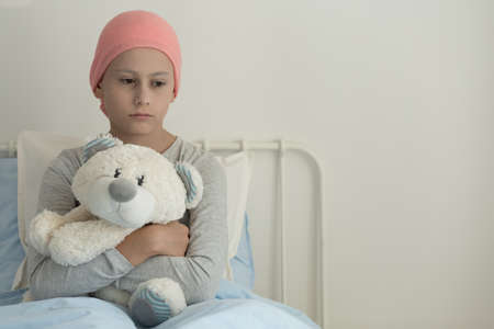 Weak girl with cancer wearing pink headscarf and hugging teddy bear next to copy space