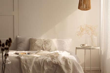 Pflanzen Sie auf dem Tisch neben dem Bett mit Kissen und Laken in weißem, einfachem Schlafzimmer. Echtes Foto