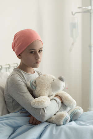 Sad lonely sick girl with cancer hugging plush toy in the hospital