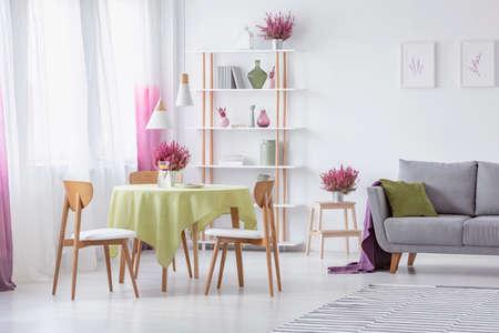 Elegancki salon z drewnianymi krzesłami, okrągły stół z oliwkowym obrusem, szara kanapa z poduszką i wrzos w doniczkach