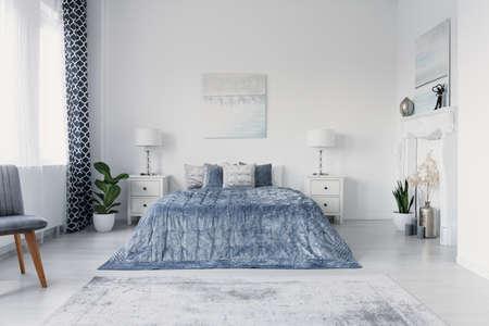 Schmerzen über großem bequemem Bett im Luxusschlafzimmer im New Yorker Stil, echtes Foto
