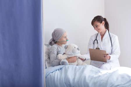 Doctor sonriente con estetoscopio hablando con niño con cáncer abrazando peluche