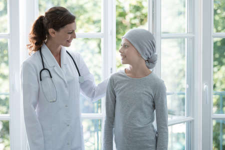 Happy doctor supporting positive child with cancer wearing headscarf Stock Photo