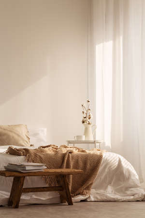 Wooden stool in front of bed with blanket in natural white bedroom interior with plant. Real photo Stock Photo