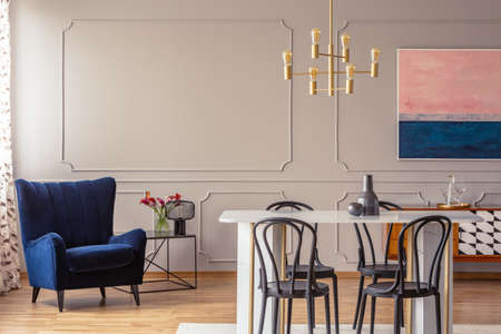 Dark blue armchair in a dining room interior with a table, chairs and golden lamp. Real photo. Empty wall, place your graphic