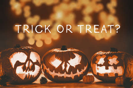 Caption trick or treat on the photo of three spooky jack-o-lanterns made for halloween Stock fotó