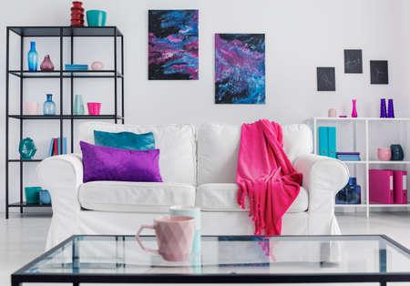 Tasse rose sur table devant un canapé blanc avec couverture à l'intérieur de l'appartement avec des affiches. Vrai photo