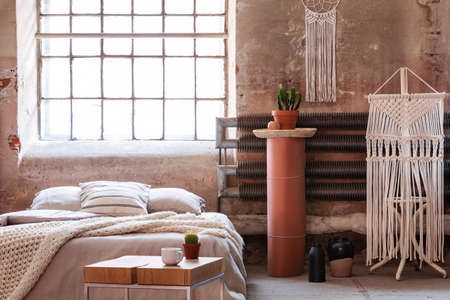 Macrame in a wabi sabi bedroom interior with a bed, table and stand with a plant. Real photo Foto de archivo