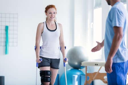 Donna che cammina con le stampelle durante la fisioterapia Archivio Fotografico