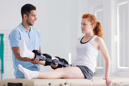 Young woman wearing a brace during rehabilitation with her physiotherapist Banque d'images